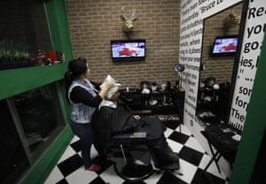Paula Noriega (left) looks up at a screen displaying the US elections results as she dries the hair of Alan Maldonado at a barber shop