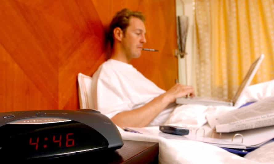 man working with laptop in bed