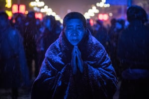 A Buddhist nun prays in front of a giant TV screen showing a ceremony with sculptures made of yak butter