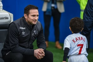The Derby manager, Frank Lampard, smiles at a mascot before their game with Brighton at the Amex Stadium