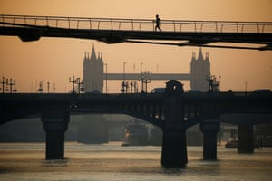 London, England: A runner crosses the Millennium Bridge in the early morning