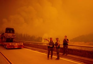 """Law enforcement and fire personnel wait on the Enterprise Bridge to enter an area encroached by fire during the Bear fire, part of the North Lightning Complex fires, in unincorporated Butte County, in Oroville, California on September 9, 2020. - More than 300,000 acres are burning across the northwestern state including 35 major wildfires, with at least five towns """"substantially destroyed"""" and mass evacuations taking place."""