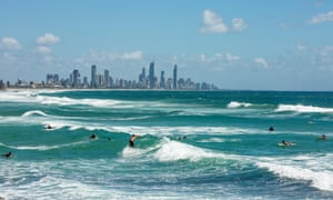 Surfers at Burleigh Heads, with Gold Coast resort of Surfers Paradise in the distance.