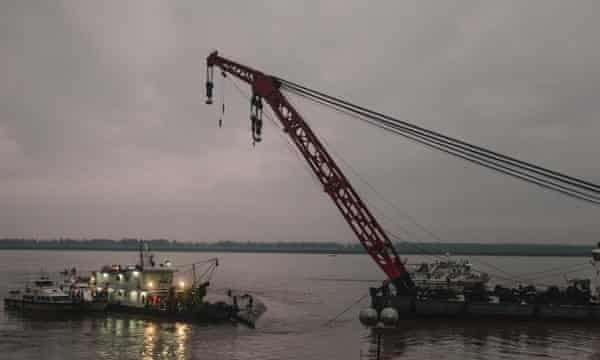 A giant crane supports the ship as rescuers cut into the hull.