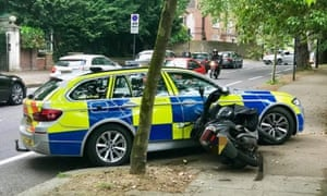 A moped that has been stopped by a police vehicle following a pursuit