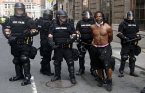 Overdressed police holding an underdressed protester.