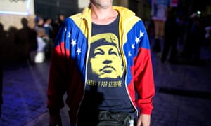 A pro-government supporter wears a T-Shirt with image of Venezuela's late President Hugo Chavez, as he waits for resultsof the elections in Caracas.