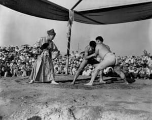 A referee in traditional attire watches over a sumo competition attended by many of the internees at the relocation camp in Santa Anita, California in 1942
