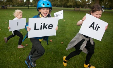 children run outside with signs that read