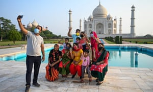A group of tourists take souvenir photos at the Taj Mahal after it reopened to visitors following authorities easing Covid-19 coronavirus restrictions in Agra on 16 June.