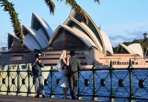 Sydney, AustraliaA couple have their wedding photos taken beside the harbour with the Opera House in the background. The NSW government has eased COVID-19 lockdown measures in response to a decline in coronavirus cases across the state. From today two adults and dependant children will be allowed to visit another household to reduce social isolation and improve mental health but social distancing measures must still be observed and extra care should be take when visiting anyone over the age of 70