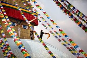 A pilgrim spreads prayer flags at the Boudhanath stupa in Kathmandu, Nepal