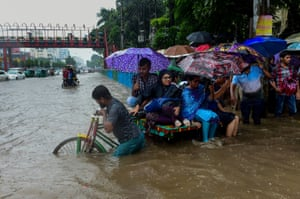 Bangladeshi commuters use a rickshaw to cross a flooded street amid heavy rainfall in Dhaka in July 2017.