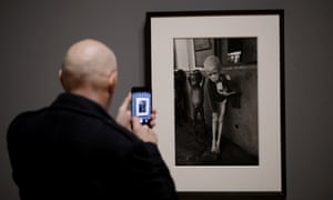 A visitor takes a photo of a 1968 photograph of a starving albino boy in Biafra by Don McCullin.
