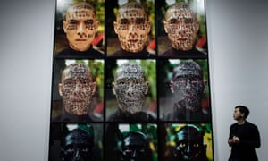A man stands by an artwork by Chinese artist Zhang Huan titled Family Tree during the preview of the M+ Sigg art show in Hong Kong.