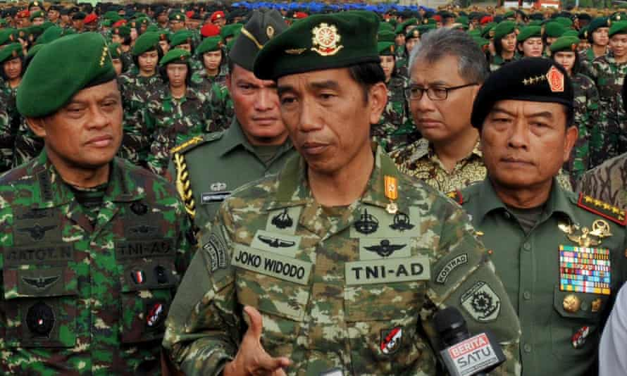 Indonesian President Joko Widodo (C), in full military uniform, standing with Army Chief General Gatot Nurmantyo (L) and Armed Forces Chief General Moeldoko (R) before a formation of female army troops to lead the ceremony of the construction of a military hospital in Jakarta.