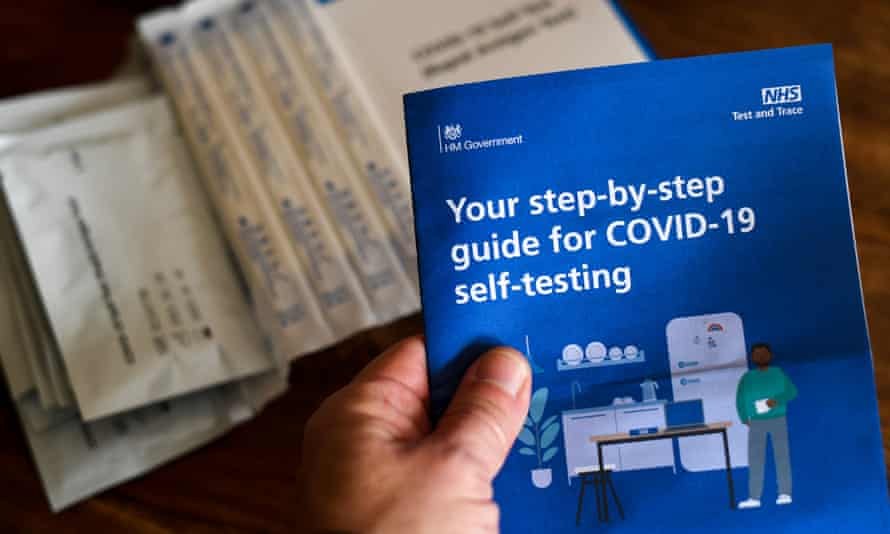 A hand is seen holding a guide for Covid self-testing