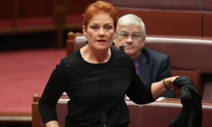 Pauline Hanson removes a burqa during question time in the Senate