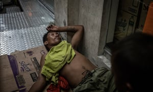 """A man under the influence of drugs has passed out in front of a store entrance, a highly dangerous thing to do in Navotas. where there have been dozens of extrajudicial killings since the beginning of Duterte's """"Tokhang"""" drug war"""