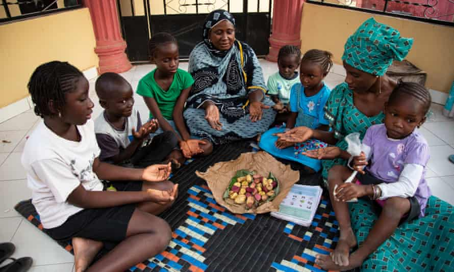 Oumie Sissokho, an FGM activist in the Gambia, prepares to discuss the practice with a family