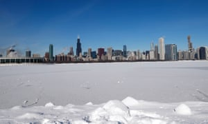 Steam rises from the buildings as Lake Michigan is covered in ice and snow