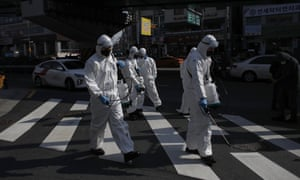South Korean soldiers wearing protective gears spray disinfectant as a precaution against the new coronavirus on a street in Seoul.