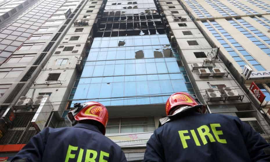 Firefighters outside the burned-out tower in Dhaka