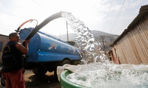 A man delivers water from a water tank in San Juan de Miraflores on the outskirts of Lima.