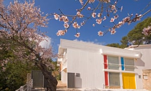 Exterior of the colourful Miró Mallorca Fundació​​, Palma, surrounded by cherry blossom on a blue-sky day.