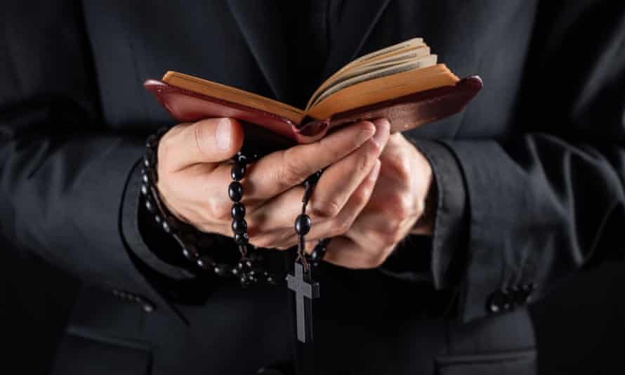 A priest's hands holding a crucifix and bible