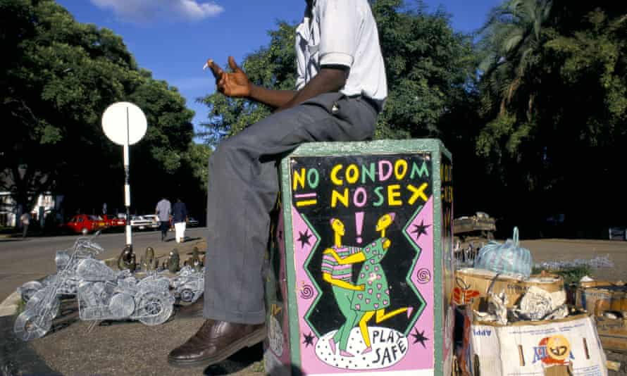 A seller in Bulawayo, the second-largest city in Zimbabwe, sits above a condom awareness poster.