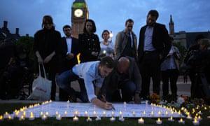 Members of the public sign a white board of condolences at a vigil for Jo Cox in Parliament Square.