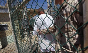 A US military guard moves an 'enemy combatant' within the detention center.