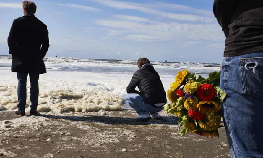 Relatives, friends and the surf community gather on The Hague beach where five surfers drowned during a storm.