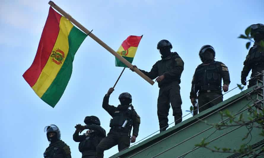 Bolivian police wave flags from a roof in Cochabamba, Bolivia.