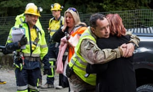 Family members and workers hug after the re-opening of the entrance to the Pike River Mine where 29 miners lost their lives in an explosion in 2010.