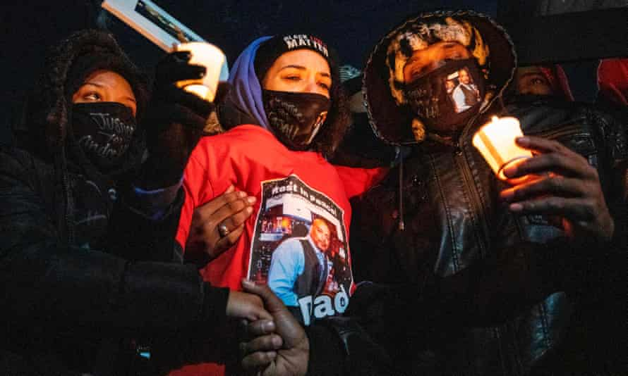 Karissa Hill, center, Andre Hill's daughter, is comforted during a candlelight vigil to honor her father, who was killed by police on 21 December.