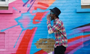 Black man in sunglasses shouting near colorful wall