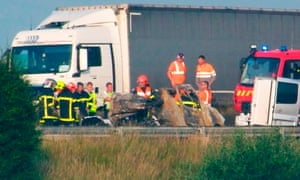 Firefighters assess the wreckage of a van that burst into flames following a crash on the A16 in northern France, killing the driver.