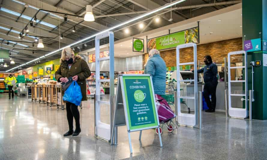Customers at a Morrisons supermarket with sign instructing shoppers to wear face masks
