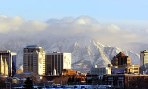 The downtown buildings of Salt Lake City glow in the setting sun with the Wasatch mountain range looming in the background.