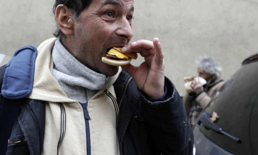 Homeless people eat hamburgers outside a Medicina Solidale centre in Rome