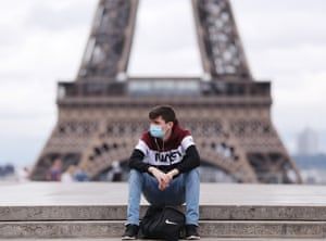 A man wearing a face mask rests at the Trocadero Palace near the Eiffel Tower in Paris, France, on 10 July, 2020.