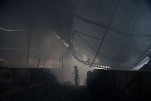 A firefighter tries to put out the blaze which destroyed the iron market.