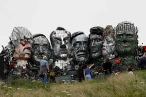 People look at a giant Mount Rushmore-style sculpture of the G7 leaders heads, made entirely of discarded electronics, on a beach near Carbis Bay to highlight the huge environmental threat of electronic waste ahead of the G7 summit