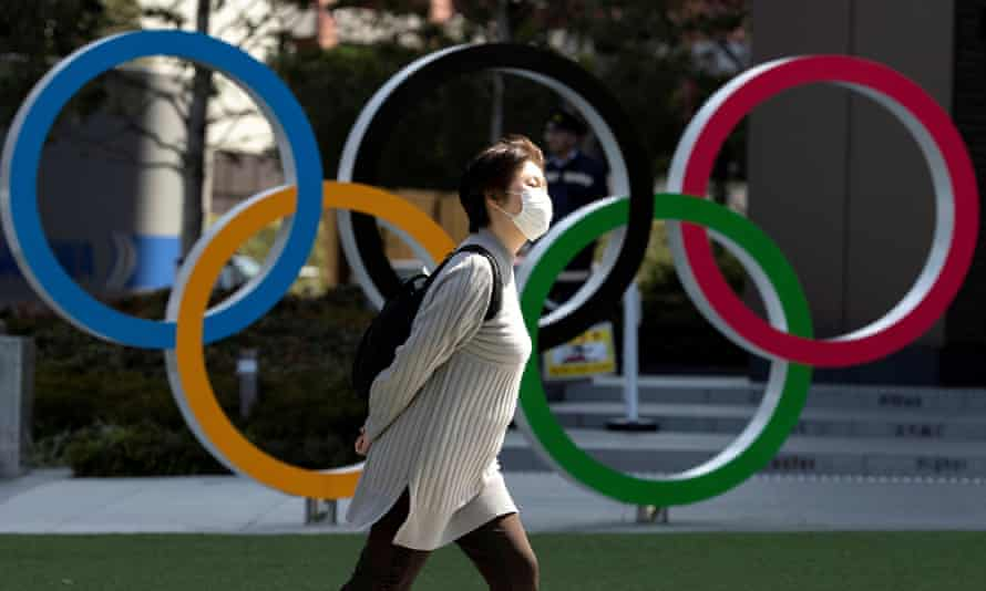 A woman wearing a protective face mask walks past the Olympic rings in Tokyo