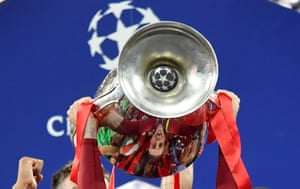 Liverpool's Jordan Henderson in the reflection of the trophy as they celebrate after winning the Champions League.