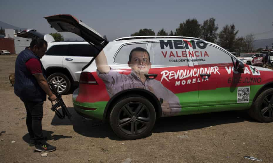 A bodyguard of Institutional Revolutionary Party, PRI, mayoral candidate Guillermo Valencia, takes his assault rifle from the back of the armoured SUV they travel in, during one of Valencia's campaign stops in Morelia, Michoacan state.