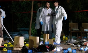 Forensic and police officers work at the site of a bomb attack in Suruç, Turkey.