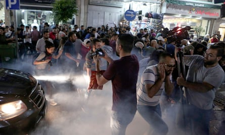 Palestinian protesters run after special police fired teargas during the protest in Ramallah on Wednesday.